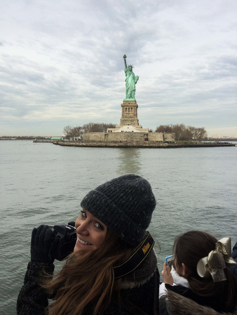 Female photographer in front of the Statue of Liberty.
