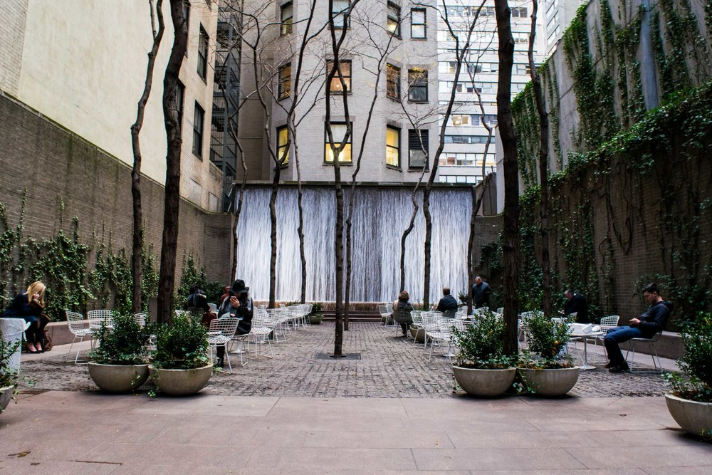 Paley Park, New York City with waterfall and people sitting at tables.