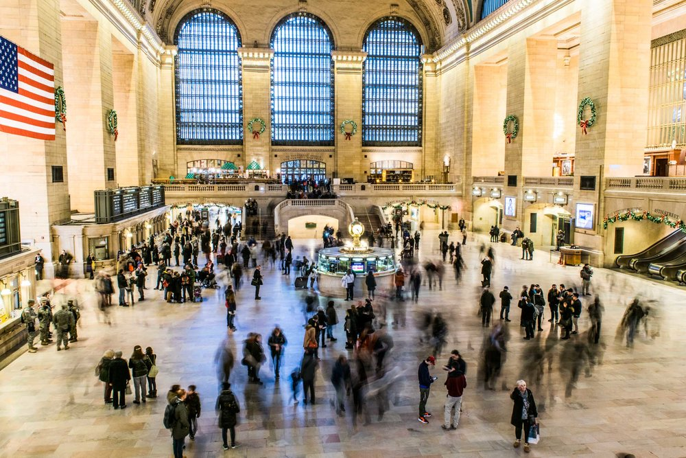 Grand Central terminal in New York City with commuters rushing through and Christmas decorations in the background.