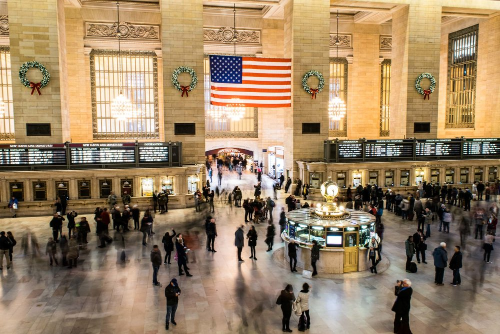 Commuters rushing through Grand Central terminal, past the information booth clock and under the American flag.
