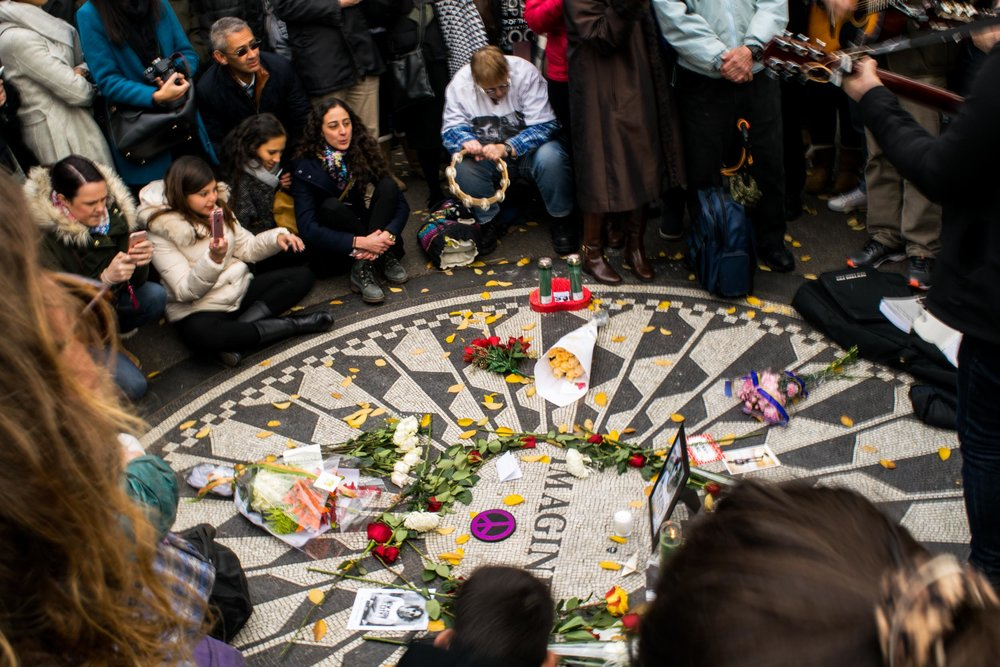 John Lennon fans gathered at Strawberry Fields in Central Park, laying flowers on the Imagine mosaic and musicians playing guitar and the tambourine.