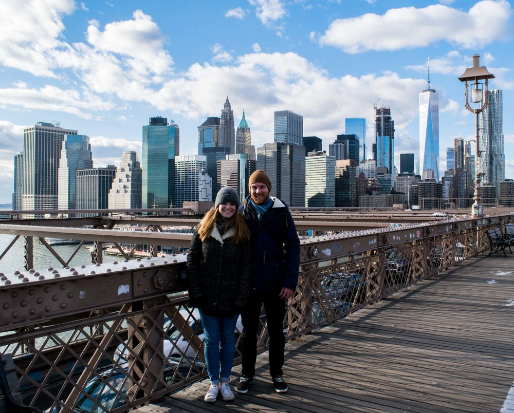 Couple stood on the Brooklyn Bridge with Manhattan skyline behind.