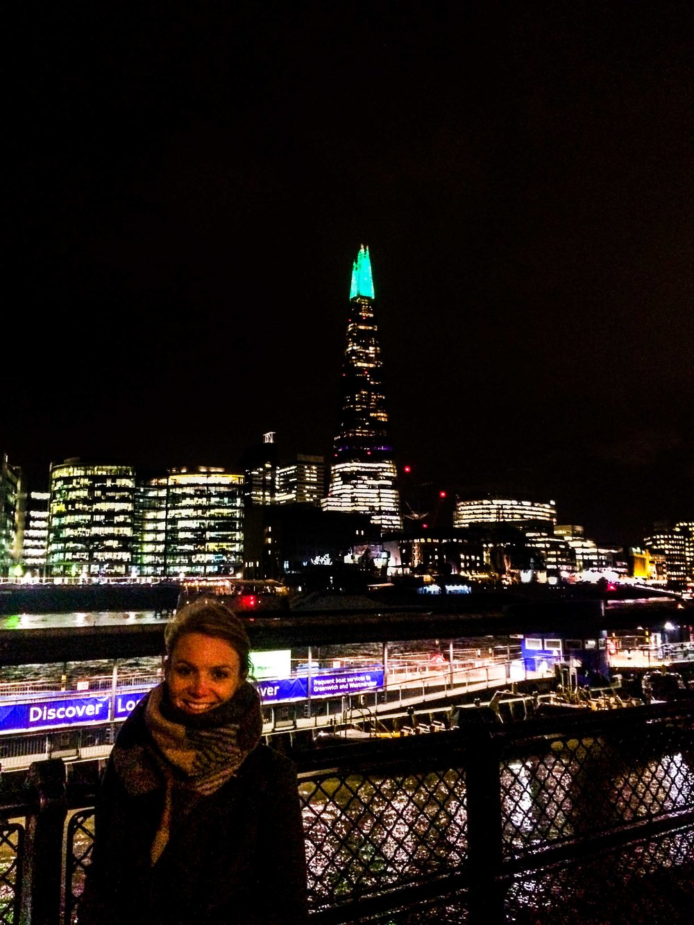 Woman standing in front of the Thames and the Shard in London at night.