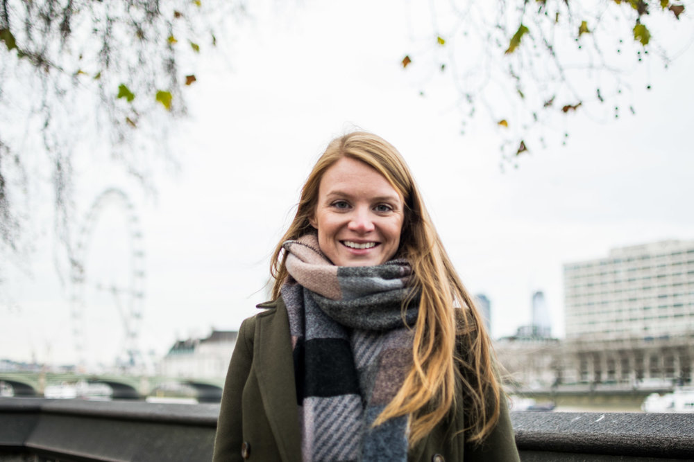 Woman with green coat and grey scarf standing in front of the River Thames and London Eye.