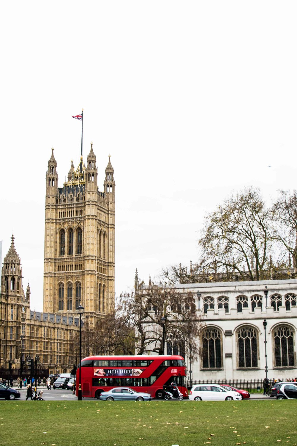 London red bus driving by the Houses of Parliament and House of Lords