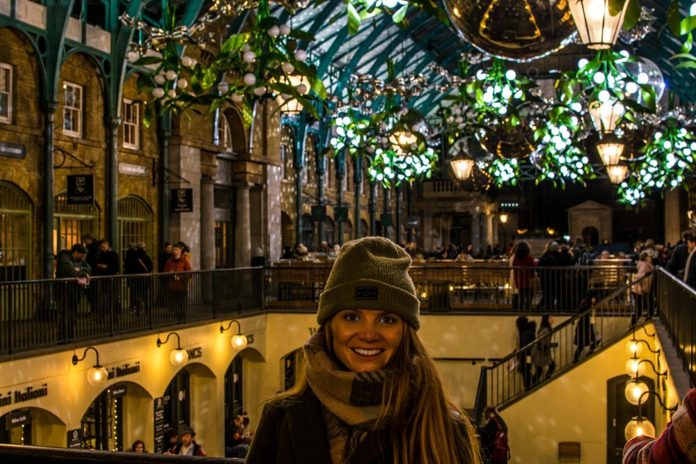 Woman in Covent Garden Market with Christmas lights behind.