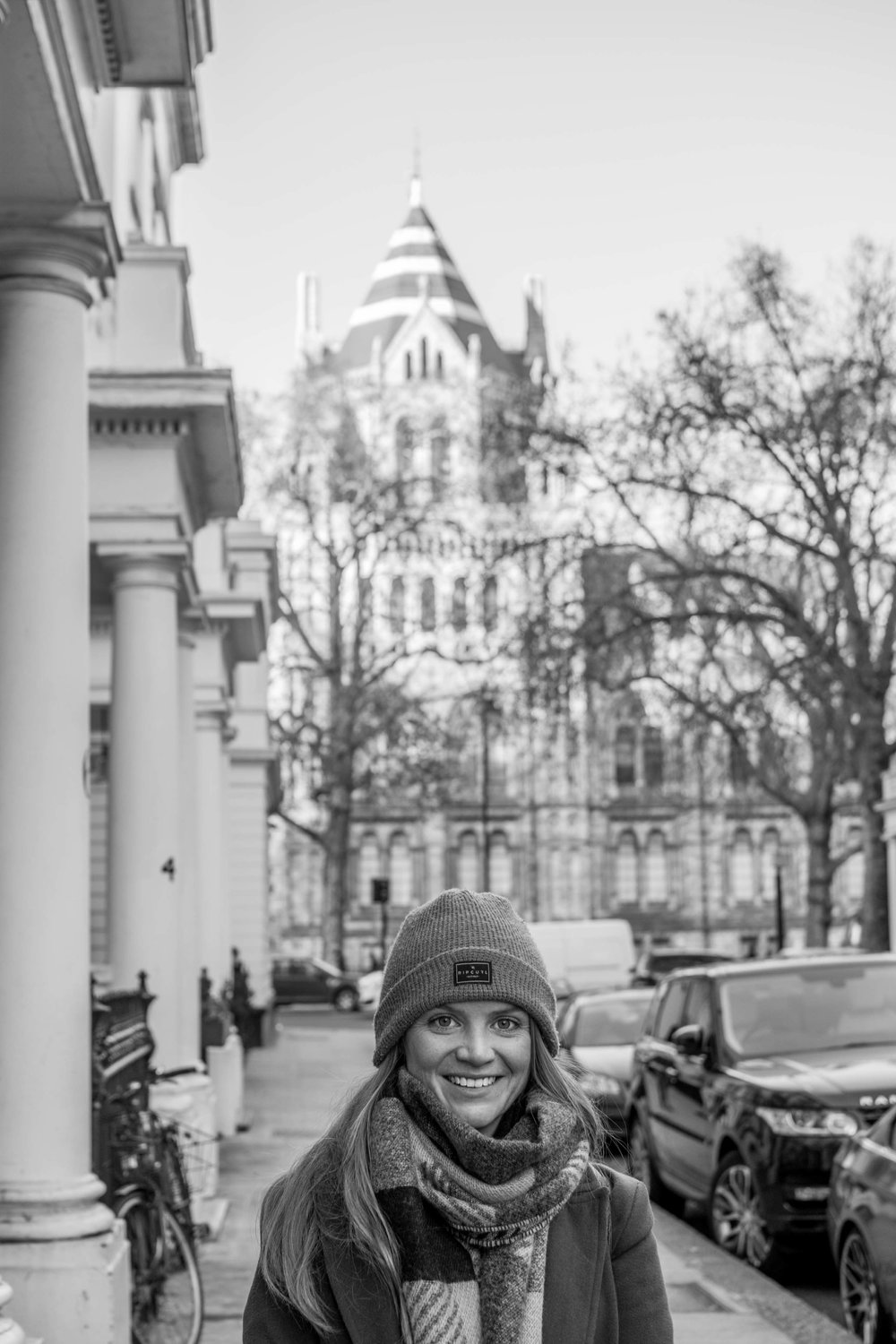 Woman in South Kensington with the Natural History Museum in the background, black and white.