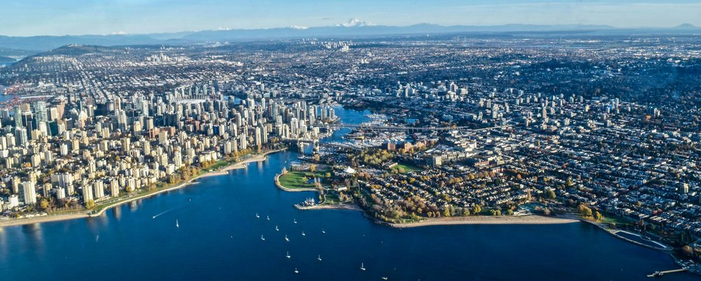 Aerial view over Vancouver, BC with boats sailing into False Creek. Taken on a Harbour Air seaplane.
