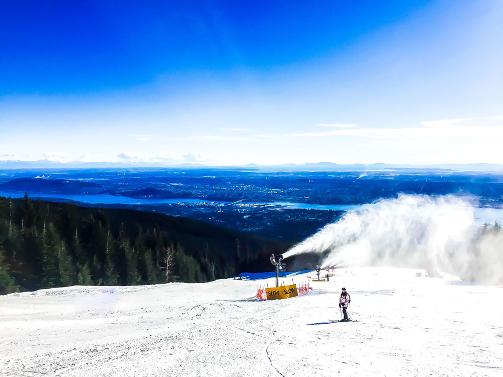 Woman skiing on Grouse Mountain with the view of the city and sea below and snow gun behind. Vancouver.