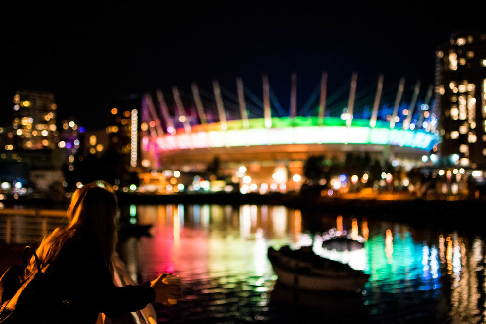 Woman looking at BC Place at night in Vancouver's False Creek, stopping on the seawall.