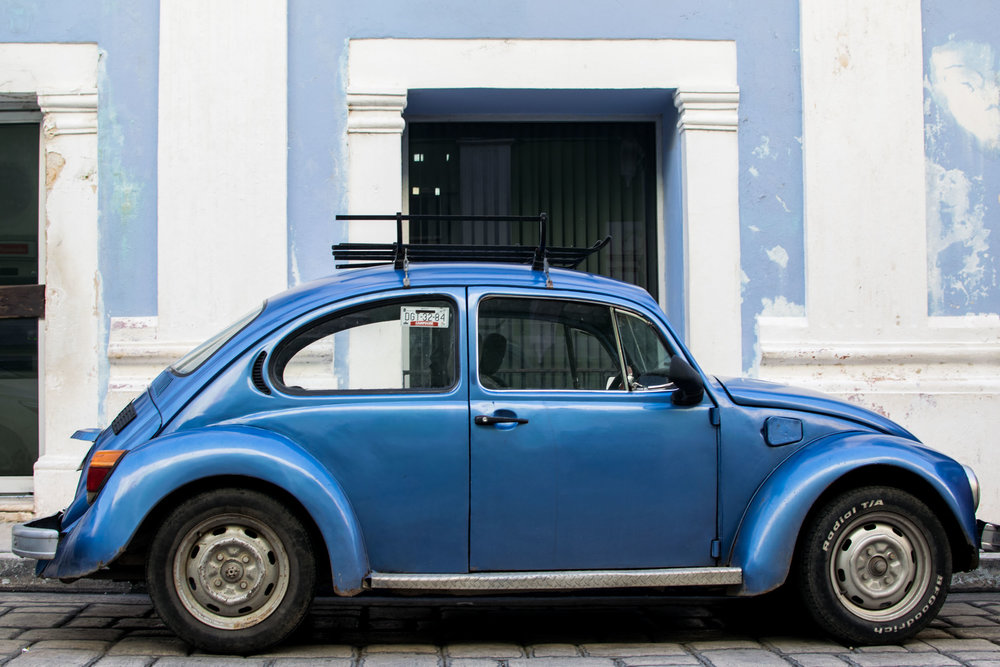 Blue VW Beatles against a pastel blue wall in Campeche, Mexico.