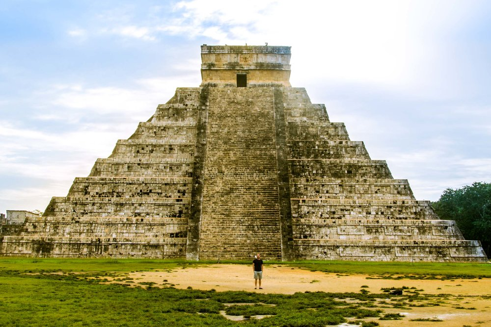Man standing in front of El Castillo, the main pyramid in the Mayan ruin site Chichen Itza, Mexico.
