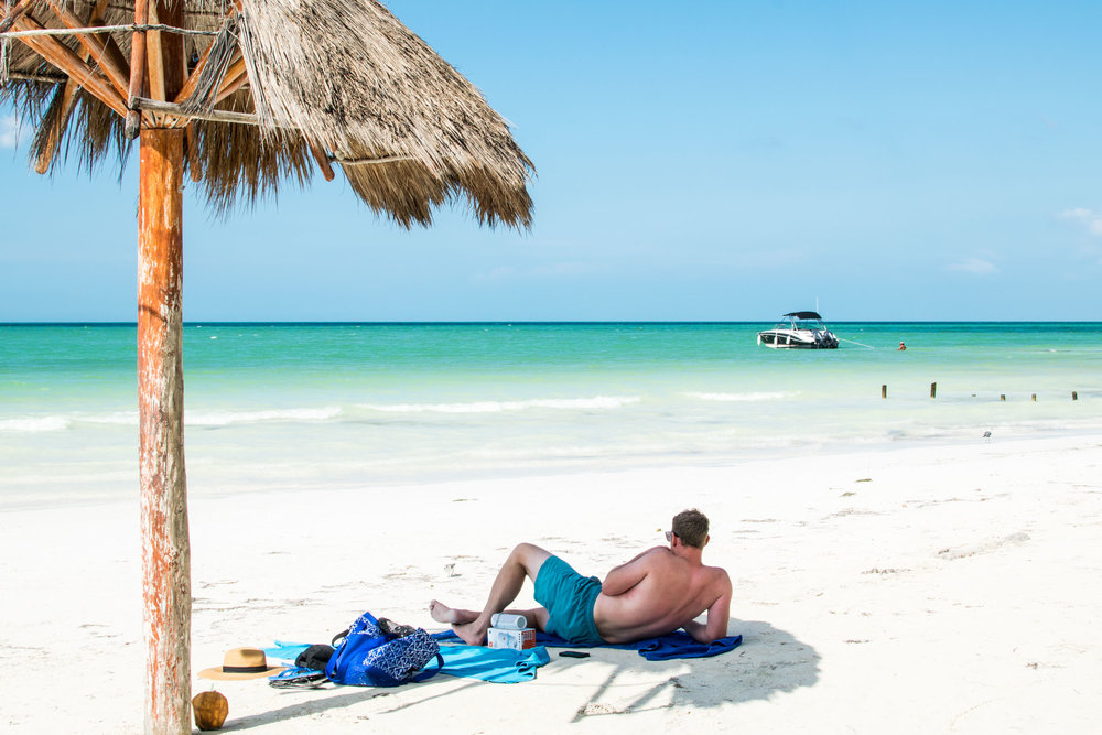 Man sunbathing on a white sand beach with blue waters and a boat in the distance. Isla Holbox, Mexico.
