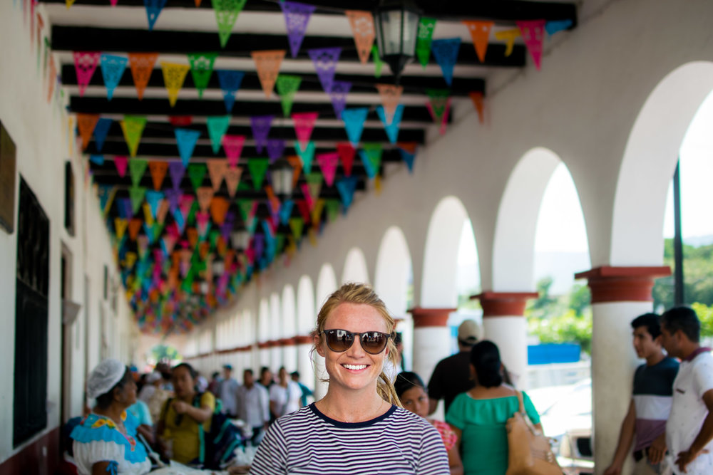 Woman standing by outdoor market stalls, under multicoloured flags and in front of pillars. Chiapa de Corzo, Mexico.