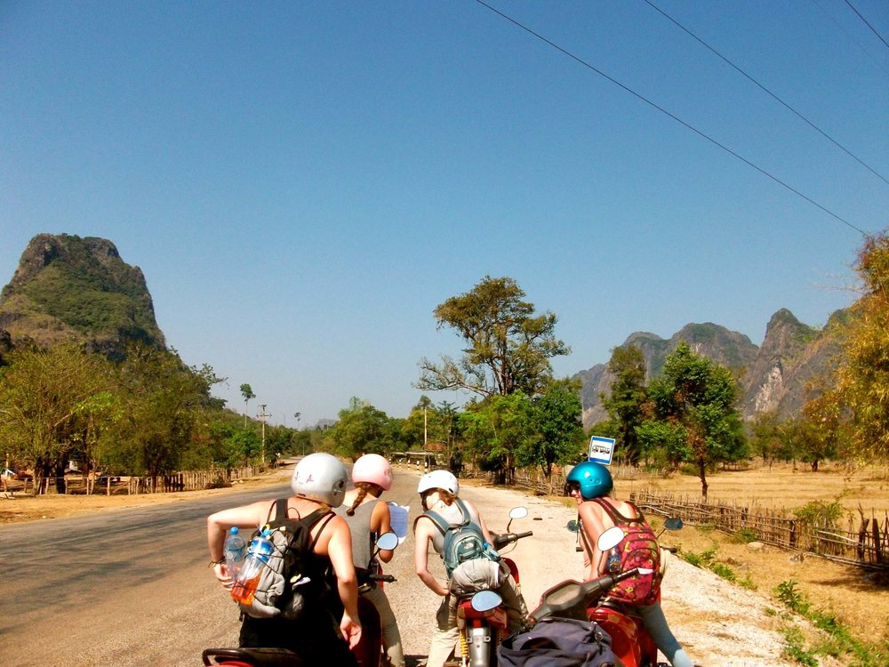 "4 women consulting their map while motorbiking 'The Loop"" trek in Laos."