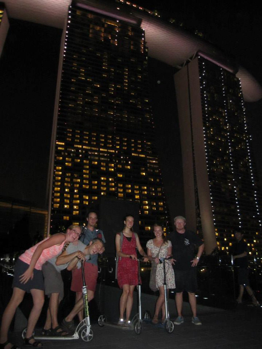 Group of adults on a scooter tour of Singapore, courtesy of the InnCrowd Backpackers Hostel.