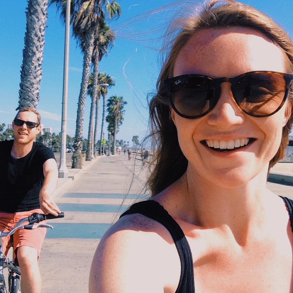 Couple cycling the track in Santa Monica beneath the palm trees. California, USA.