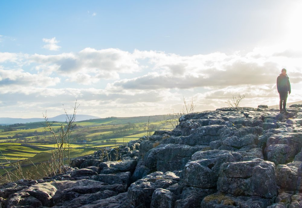 Man stood on the Limestone Pavement at Malham Cove, Yorkshire, England.