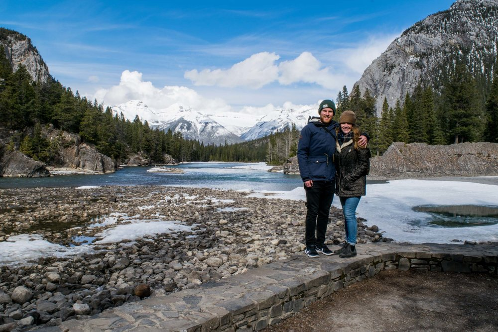 Couple stood beside the Bow River with Tunnel Mountain behind. Banff, Alberta, Canada.