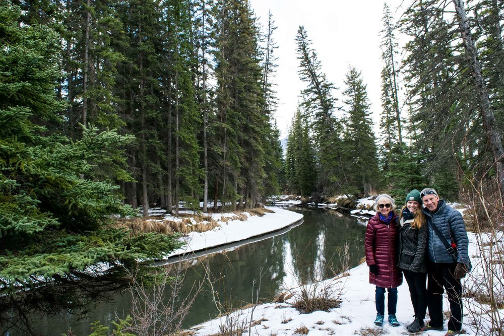 Family stood in the snow by the Forty Mile Creek on the Fenland Trail, Banff, Alberta, Canada.