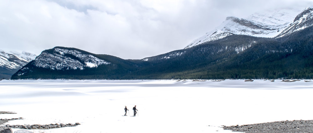 Couple snow-shoeing on a frozen Spray Lakes Reservoir, near Canmore in Alberta, Canada. Rocky Mountains.