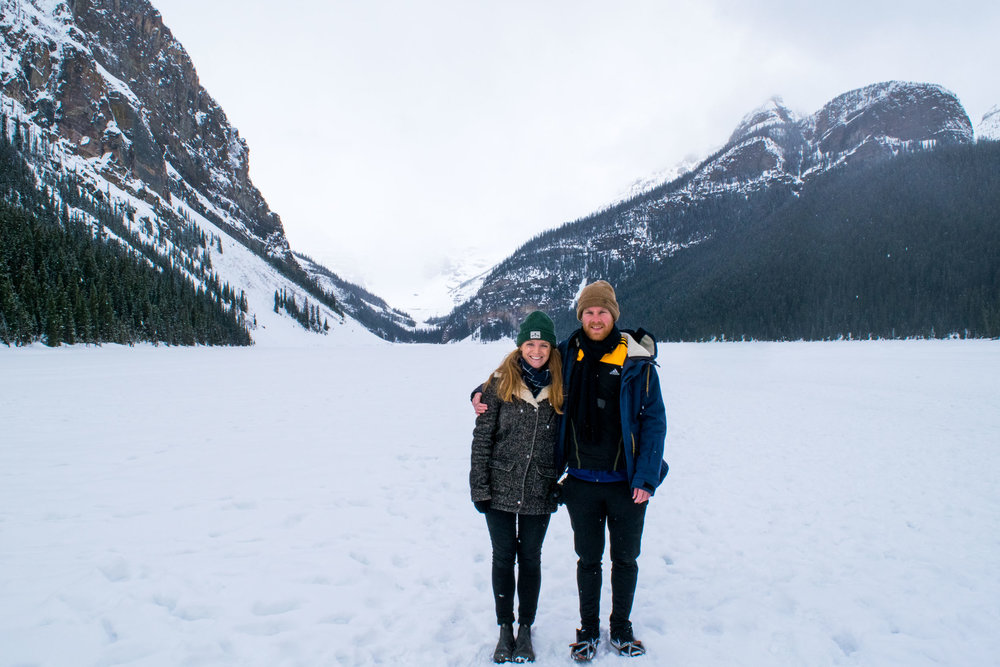 Couple stood on a frozen Lake Louise, near Banff, Alberta, Canada.
