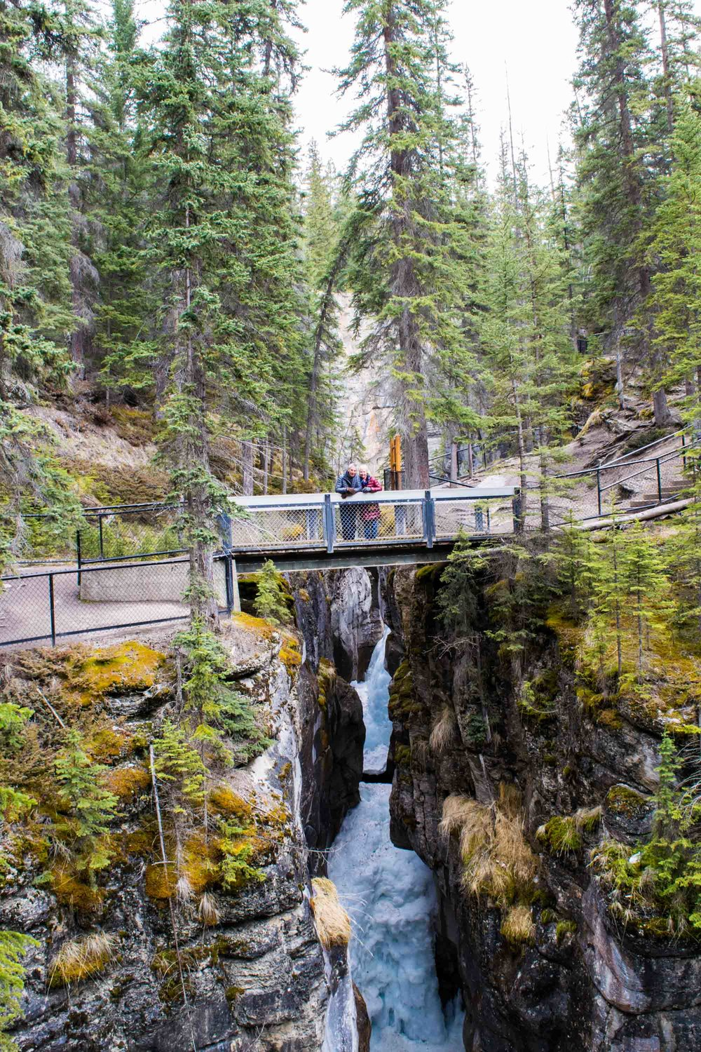 Couple stood on a bridge over the Maligne Canyon in Jasper National Park. Alberta, Canada.