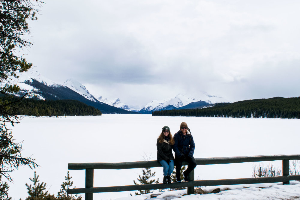 Couple sitting on a fence with a frozen and snowy Maligne Lake behind. Jasper National Park, Alberta, Canada.