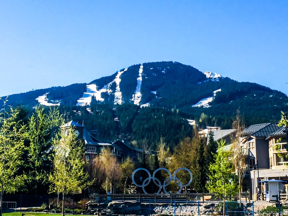 Whistler village with Whistler mountain in the background and Olympic rings from their hosting of the 2010 Winter Olympics in the foreground. British Columbia, Canada.