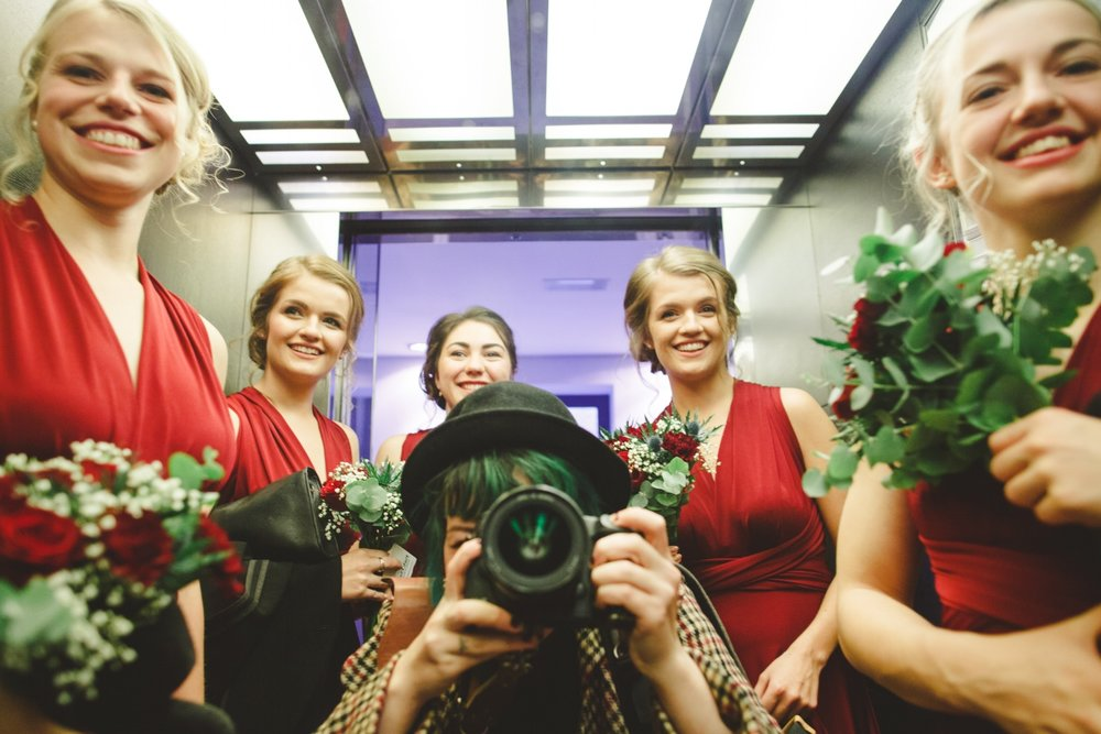Alternative wedding photographer with bridesmaids in red dresses taking photograph