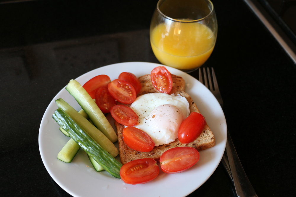 Cucumber sticks, cherry tomatoes, a slice of brown toast, one poached egg and a small glass of orange juice.