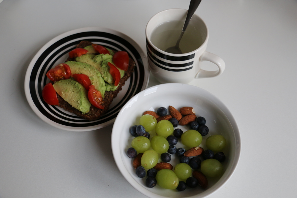 One slice of rye bread with half and avocado, cherry tomatoes, 10 grapes, 10 almonds and a small handful of blueberries. Also drinking a cup of hot water.