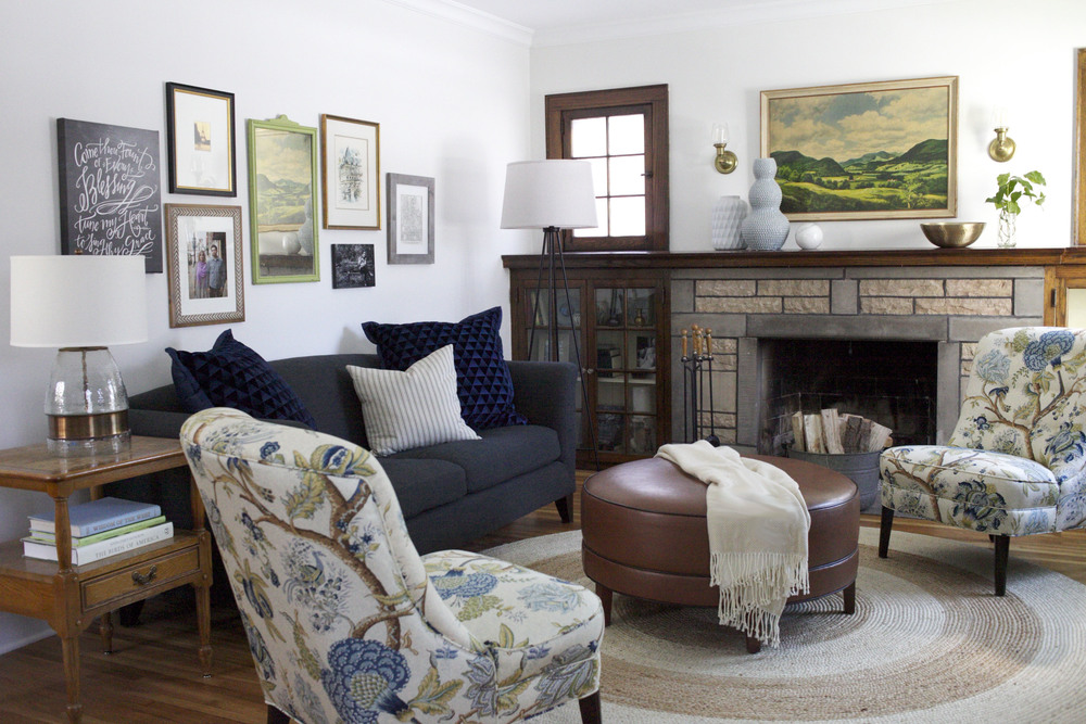 Neutral Living Room with stone fireplace, round leather ottoman, slipper chairs, navy couch, and salon style wall
