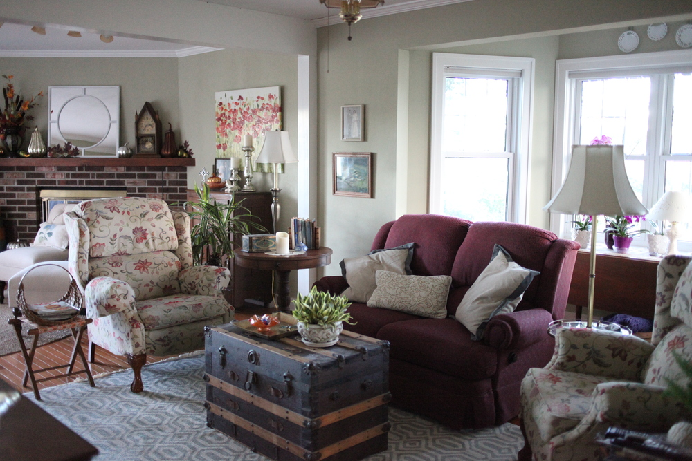 Cozy farmhouse living room with antique trunk, modern rug, sage walls, loveseat, and throw pillows