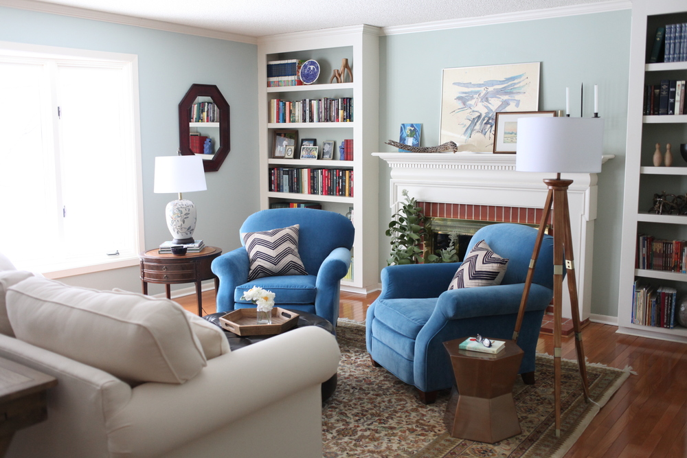 Blue velvet club chairs in traditional yet modern living room with brick fireplace and neutral Persian rug