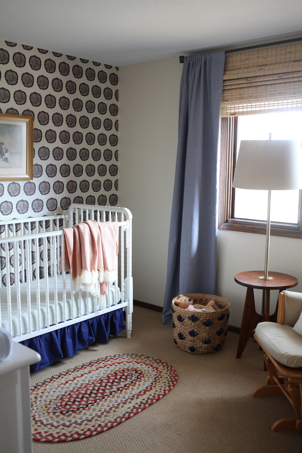 Modern nursery with wood design Spoonflower wallpaper, blue gingham curtains, white Lind crib, colorful rag rug and basket