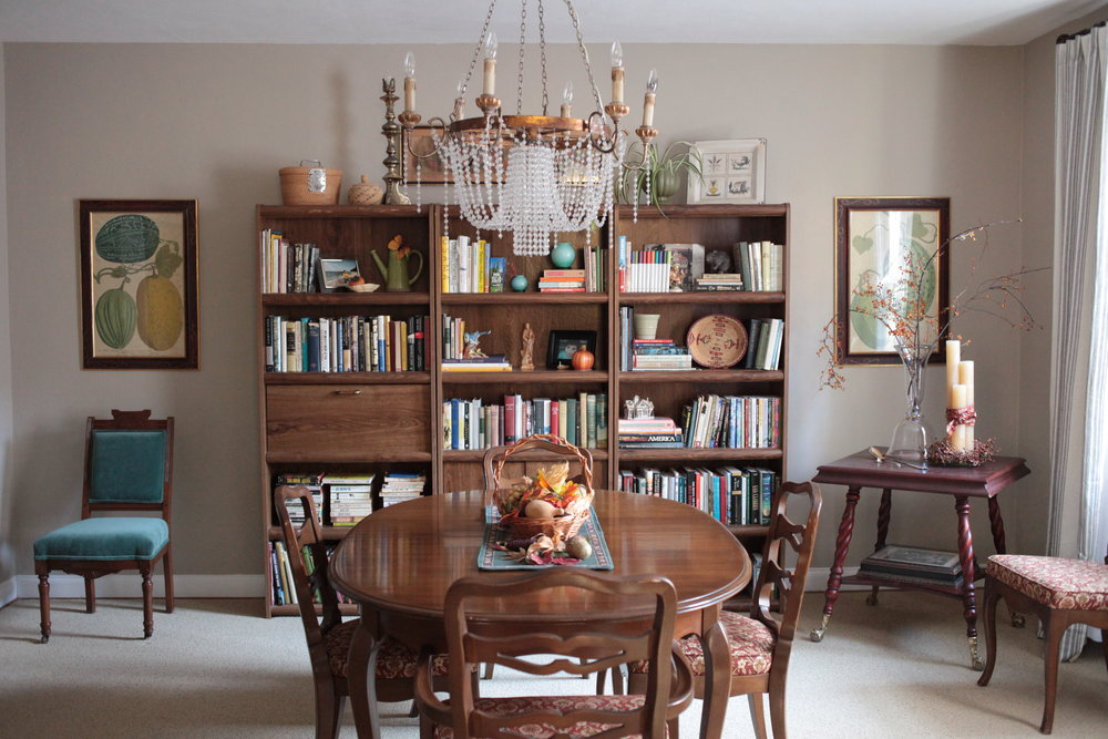 Traditional dining room with, blue velvet chair, crystal chandelier, and styled bookshelves