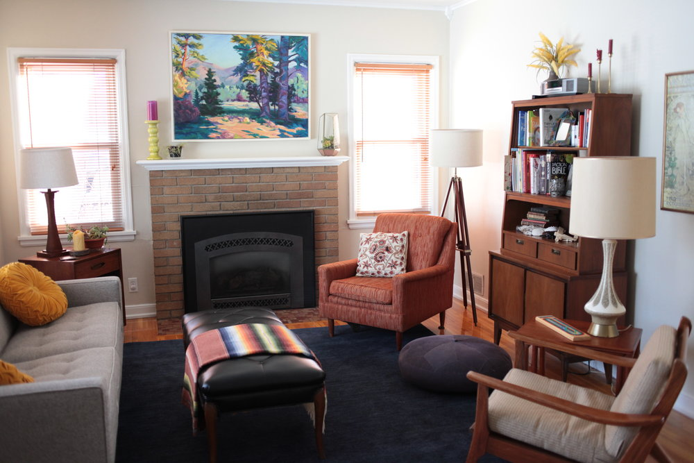 Mid Century Modern living room with deep blue rug, vintage furniture, MCM hutch, and original oil painting