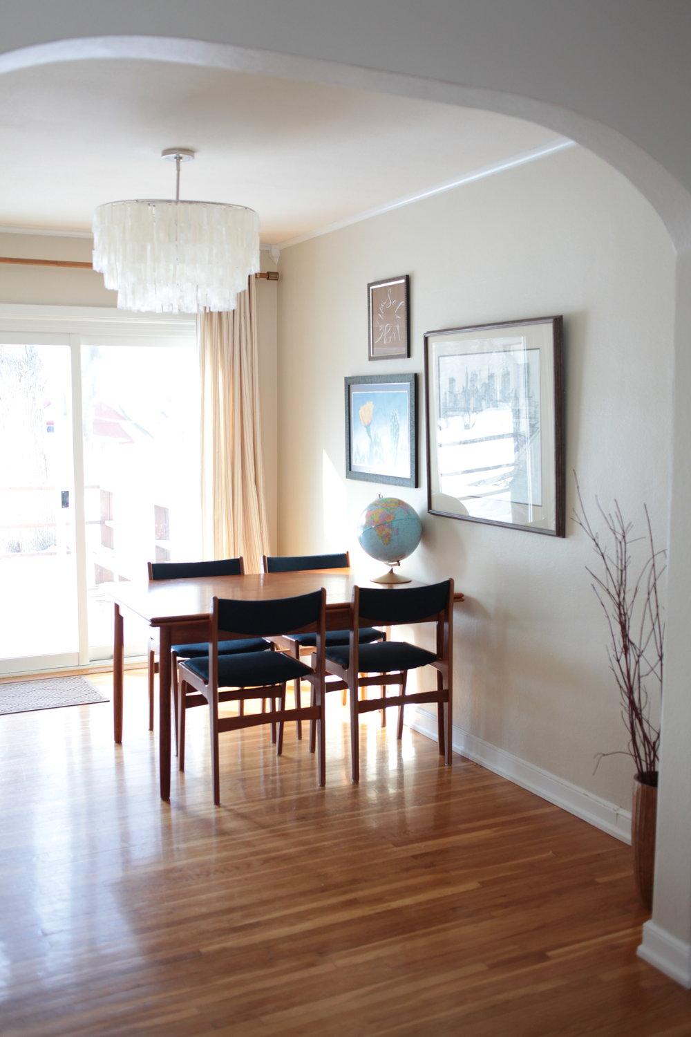 Mid Century Modern dining room with West Elm capriz chandelier, gallery wall, and blue dining chairs