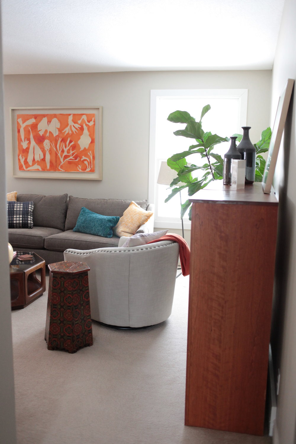 A neutral living room with large orange art and Pottery Barn Harlow swivel chair .JPG