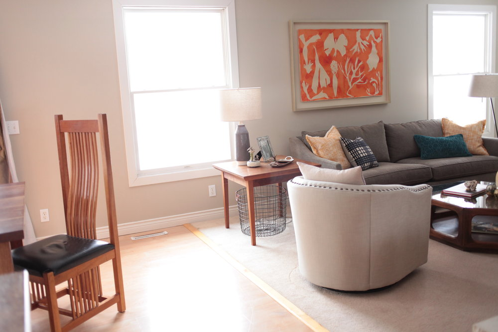 A neutral living room with large orange art and Pottery Barn Harlow swivel chair.JPG