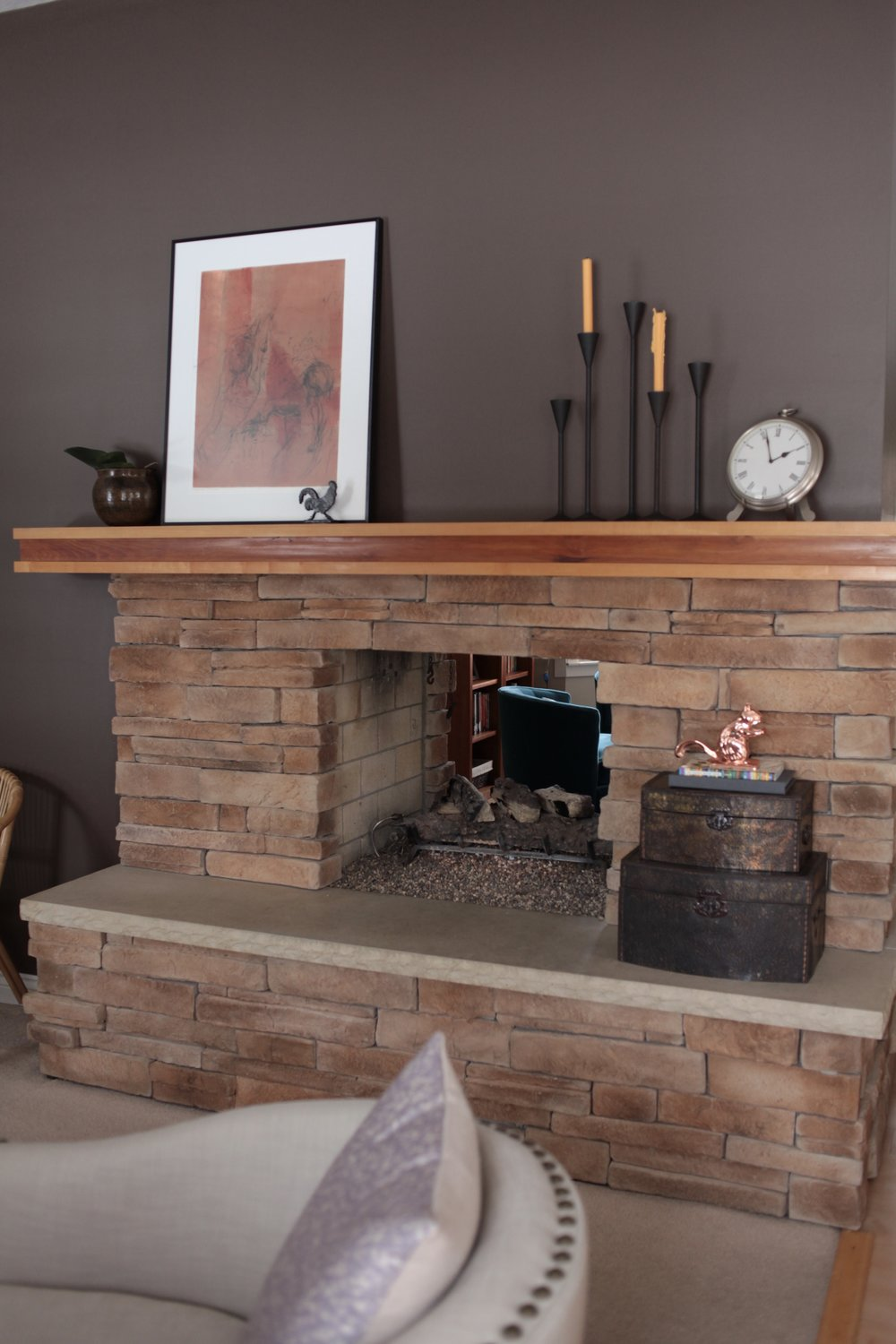 Styled large fireplace with modern black candlesticks and orange art.jpeg