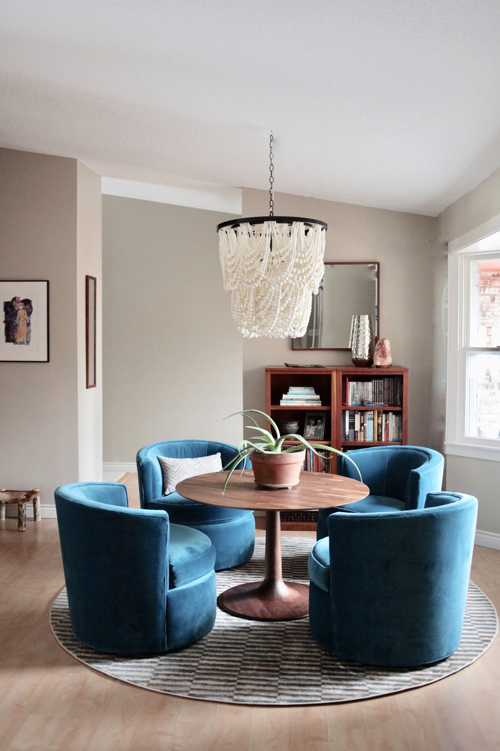 Modern blue velvet Room & Board Otis chairs with round wood table and Pottery Barn Amelia wooden beaded chandelier.jpeg
