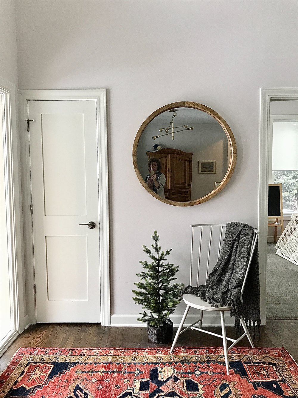 entrance hall with round mirror and vintage wool rug