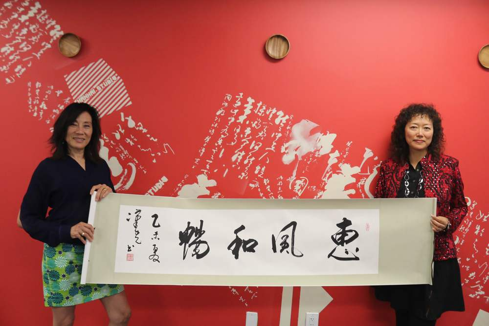 Janet Yang(Left) and Kelly Zhang are holding Mr. Hanguang Wang's calligraphy at Hanhai Studio.