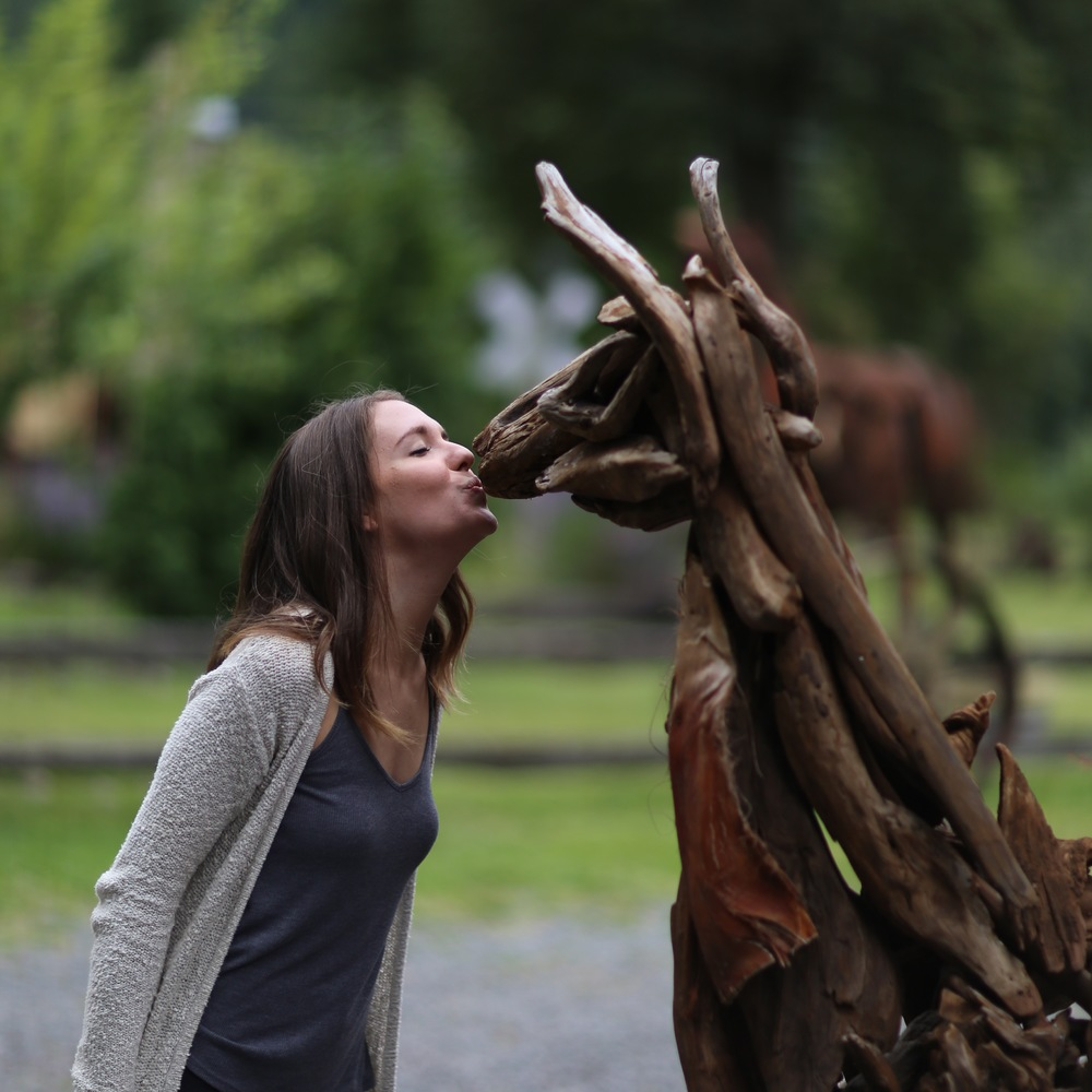 Sarah Nelson kisses a wooden lama