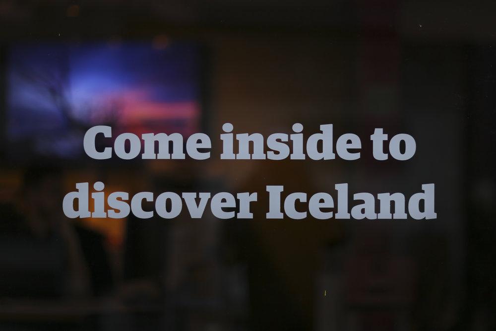 """Come inside to discover Iceland"" sign on a tourist bureau window"