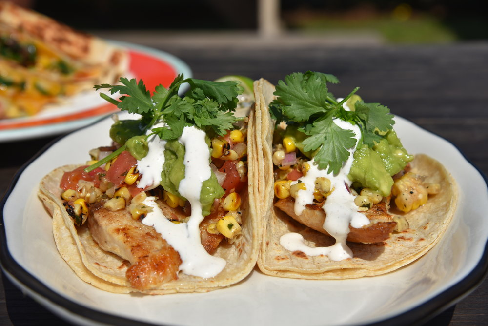 """""""Hither Creek Fish Tacos""""  Grilled striped bass in corn tortillas with tomatoes, sweet corn salad, guacamole, and lime sour cream."""