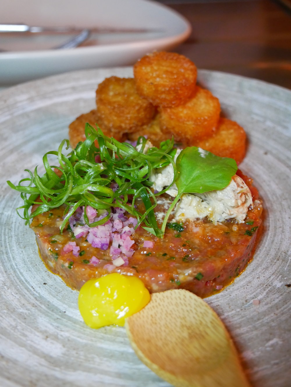 Steak tartare with tater tots, egg yolk, watercress and caramelized onion dip