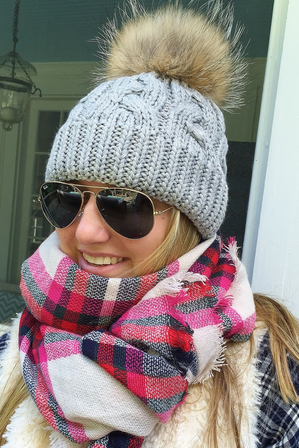 Ainsley is wearing the grey fox fur pompom knit hat and oversized preppy plaid scarf both available on the webstore!